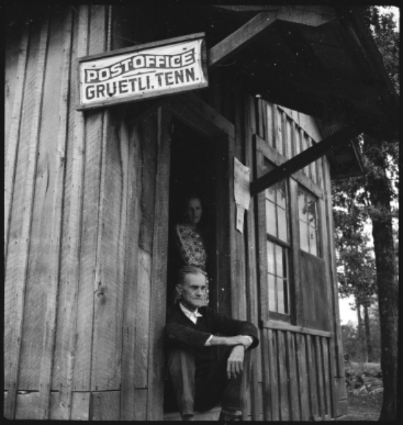"Woman and man in a wooden house with a sign saying ""Postoffice Gruetli. Tenn."""