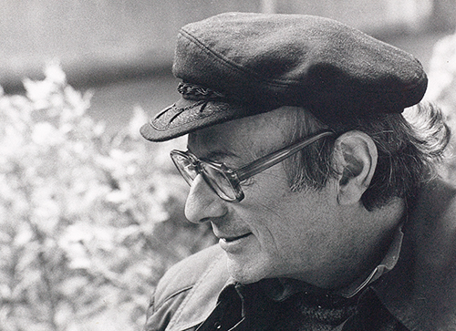 Walter Vogt wearing a peaked cap and looking downwards to the left, smiling, with a blossoming bush in the background.