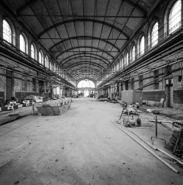 The hall of Zurich's Herdern slaughterhouse resembles a cathedral. This photograph shows the central nave. The hall has a barrel-vaulted ceiling. Its clerestory is punctuated by arched lattice windows which make the space light and elegant. Construction machinery, a skip and other building tools stand around on the floor. The photograph dates from the years 1985–87, during which the hall was renovated and transformed.