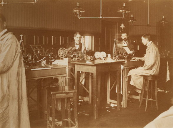 The picture shows three men working in the Bernese Telegraph Office in 1900. On a raised wooden table stand the telegraph apparatuses, around which the three men sit on raised chairs.